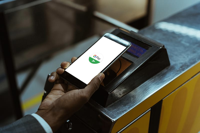 Close-up view of businessman using Google Pay paying for public